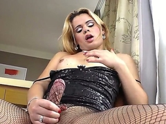 Turned on blonde shemale whore Josiane with hot body in fishnet pantyhose and sexy dress teases and and plays with her huge meaty pecker in living room in close up.